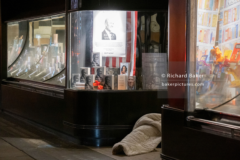 Wrapped in a sleeping bag, a homeless person lies in the doorway of Waterstones bookshop which is displaying copies of both Michelle and Barack Obama's bestselling books ('Becoming' and 'A Promised Land' respectively), on Piccadilly, on 2nd February 2021, in London, England.