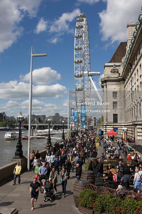 Tourist crowds walk along London's Southbank beneath the Millennium Wheel.