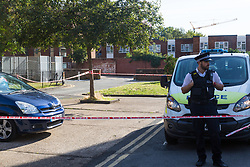 A cordon remains in place around the scene of a knife fight that left four teenagers injured on the Elmington Estate, between Marvell House and Landor House. London, August 17 2018.