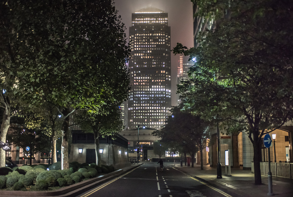 London, UK - 18 September 2014: skyscraper with illuminated windows in the financial district of Canary Wharf on a foggy night
