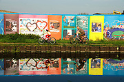Hackney, London. Olympic games site next to canal, Hackney East London. Painted hoardings reflected in the canal.