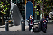 Two Asian gentlemen pause during their working day outside the leadenhall Building, on 14th August 2017, in London, England.