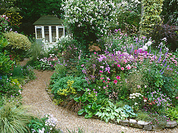General view of the garden at Ladywood with summer borders in full bloom. Wooden summerhouse. Design: Sue Ward