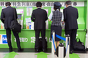 business people buying train tickets from vending machine with an attendant standing by to help Japan
