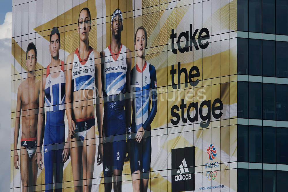 The giant presence of Team GB role-model athlete heroes on the side of the their HQ at the Westfield City shopping complex, Stratford that leads to the Olympic Park during the London 2012 Olympics, the 30th Olympiad. The ad is for sports footwear brand Adidas and their 'Take The Stage' campaign. The faces include diver Tom Daley, gymnast Louis Smith and the darling of British athletics, heptathlete gold medallist Jessica Ennis