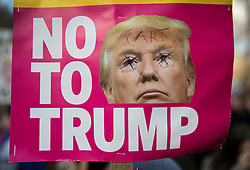 © Licensed to London News Pictures. 04/02/2017. London, UK. Protestors carry a banner mocking President Trump as they gather outside Downing Street in a demonstration against U.S President Donald Trump's Executive Order banning refugees and immigrants from a number of Muslim-majority countries. Protestors join campaign groups including Stop the War, Stand up to Racism, Muslim Association of Britain, in a march from the U.S Embassy in London to Downing Street. Photo credit: Peter Macdiarmid/LNP