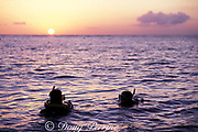 scuba divers begin night dive at sunset, La Ceiba reef, Cozumel, Mexico ( Caribbean Sea )