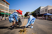 "30 JUNE 2012 - PRESCOTT, AZ:   ""Pooper Scoopers"" pick up horse dung during the Prescott Frontier Days Rodeo Parade. The pooper scoopers are among the most popular people in any parade that features lots of horses, and lots of horses march in the Prescott parade. The parade is marking its 125th year. It is one of the largest 4th of July Parades in Arizona. Prescott, about 100 miles north of Phoenix, was the first territorial capital of Arizona.   PHOTO BY JACK KURTZ"