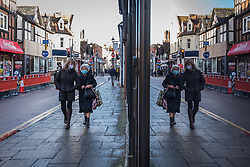 © Licensed to London News Pictures. 15/12/2020. RICKMANSWORTH, UK. Women wearing facemasks are reflected in a shop window as they walk down the high street in Rickmansworth, Hertfordshire.  The historic town will be elevated to Tier 3 Covid Alert Level tomorrow, as part of the Three Rivers District Council area joining London and other areas of the South East as the number of coronavirus cases continues to rise.  Photo credit: Stephen Chung/LNP