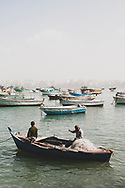 Alexandria, Egypt - February 28, 2011: Two Egyptian fishermen work on their net in the port of Alexandria. Alexandria was once one of the great cities of the Roman Empire; today it is a more humble metropolis and Egypt's second largest city.