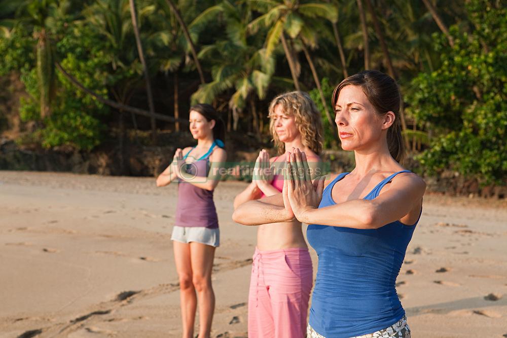 Jul. 25, 2012 - Women practicing yoga on a beach (Credit Image: © Image Source/ZUMAPRESS.com)