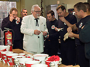 """This handout photo from KFC shows """"KFC Colonel"""" look-alike Bob Thompson eating KFC's Fiery Grilled Wings with Garfield Park fire fighters Tuesday, Jan. 5, 2010 in Indianapolis, Ind., where KFC offered to improve their fire safety by buying new fire extinguishers in exchange for putting its logos on them to promote KFC's Fiery Grilled Wings. (Photo by Brian Bohannon)"""