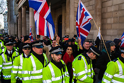 London, February 8th 2015. Muslims demonstrate outside Downing Street  to denounce the uncivilised expressionists reprinting of the cartoon image of the Holy Prophet Muhammad. PICTURED: Police escort the anti-Islamist group Britain First away from the site of the protest on Whitehall as young Muslims attempt to provoke a response.