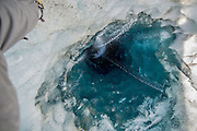 "Sinkholes on Glaciers<br /> <br /> Just like rainwater dissolves the bedrock on the Earth's crust and form sinkholes, meltwater on a glacier's surface can melt ice and form sinkholes too. Sinkholes on glaciers are called moulins, French for ""mill"". Moulins form when summer meltwater streams on the surface of the glacier finds a crevasse or other weak spot in the ice and begins to pour down through the ice. As the water moves downward, its turbulence and heat creates a narrow, tubular and vertical shaft, up to 10 meters wide, that can go all the way down to the bottom of the glacier, hundreds of meters deep. Water entering a moulin eventually exits the glacier at base level where it acts like a lubricating fluid, that plays a big role on how fast the glacier flows. The melting water accelerates the glacier's flow to the sea, where large chunks break off to form icebergs, leading to further ice loss by speeding disintegration of the ice sheet.<br /> <br /> Given enough water flow, a moulin can easily form over the course of just a month. Once formed, the shaft will stay open as long as there is meltwater to feed the moulin. If the meltwater freezes, the moulin will begin to fill up with snow and close up. Some moulins have been observed to be present in the same spot for multiple years, though the spot will constantly move forward with the flow of the ice.<br /> ©Exclusivepix Media"