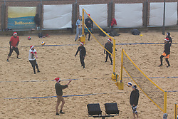 © Licensed to London News Pictures. 06/12/2015. Brighton, UK. Members of the Brighton and Hove beach volleyball club play a game of volleyball with some dressed in Santa Hats as the South Coast gets some of the fallout of storm Desmond. Today December 6th 2015. Photo credit: Hugo Michiels/LNP
