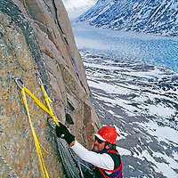 A Big Wall climber hauls heavy bags up an Arctic cliff on Baffin Island.