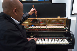 "© Licensed to London News Pictures. 26/10/2018. LONDON, UK. A piano tuner tunes a Steinway & Sons ""Victory"" upright piano, 1940-45, (Est GBP800-1,200).   Preview of ""A Private View, property from the country home of Christopher Cone and Stanley J. Seeger"" at Sotheby's, New Bond Street.  Over 200 extraordinary works will be auctioned in London on 30 October 2018.  Photo credit: Stephen Chung/LNP"