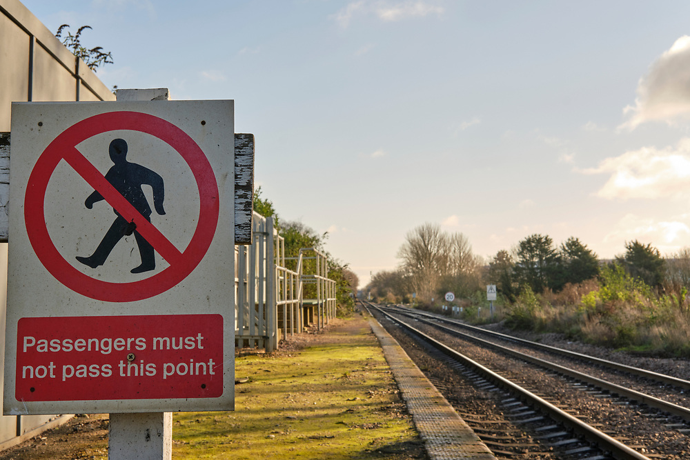 Passengers must not pass this point warning sign on the platform at Trimley Station. The line branches off the right to Felixstowe North Freightliner Terminal at Port of Felixstowe. The line directly ahead continues to Felixstowe station & the other rail freight depot at the port.<br /> <br /> Photo by Jonathan J Fussell, COPYRIGHT 2020