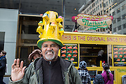 "New York, NY, USA-27 March 2016. A man wears a tall yellow hat shaped like a cylindrical bird apartment house with colored eggs at the entrances  in the annual Easter Bonnet Parade and Festival. Behind him is a Nathan's hot dog cart with the sign reading ""This is the original since 1916."""