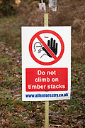 Forestry tree felling signs on Upper Hollesley Common, Suffolk, England, UK - Do not climb on timber stacks