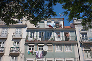 A local resident looks across the city from a balcony of his apartment building in Lisbon, Portugal.