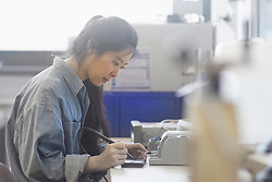 Female technician soldering electronic components in an industrial plant, Freiburg Im Breisgau, Baden-wuerttemberg, Germany