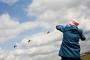 Lady plane spotter watches fly-past of the Blades aerobatic Team at Farnborough 2010 launch.