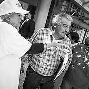 Donald Trump supporter, Shirley Thomas, left, tries to guide a latino man who just earned his citizenship papers to a table to register as a Republican. After several moments of apparent confusion, the man walked off without registering with either party.  Donald Trump has been criticized for his remarks about Mexicans and his call to build a impenetrable wall and force Mexico to pay for it.
