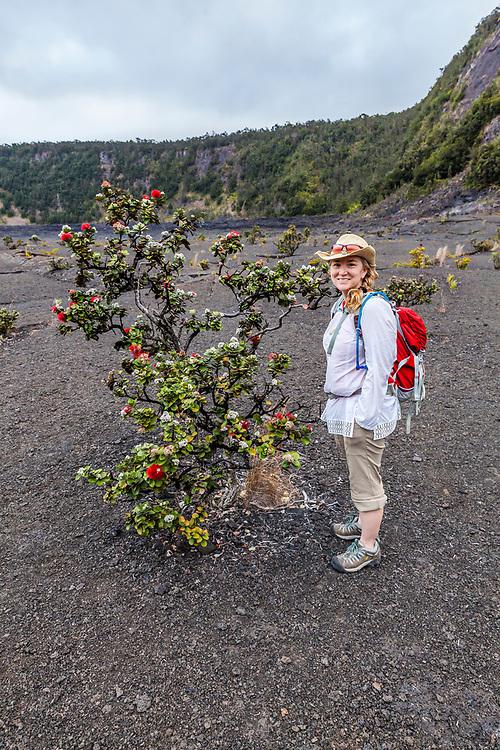 A woman standing next to a ʻōhiʻa lehu tree on the crater floor of Kilauea Iki Crater April, 2017, Hawai'i Volcanoes National Park, Hawaii, USA.