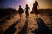 Three kids run down to the beach at sunset