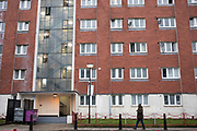 Man walks past council flats in Whitechapel, Tower Hamlets, East London on 24th February 2020 in London, United Kingdom. This area in Tower Hamlets is a poor and over populated borough with many people living in small homes of social housing in high rise apartment blocks.