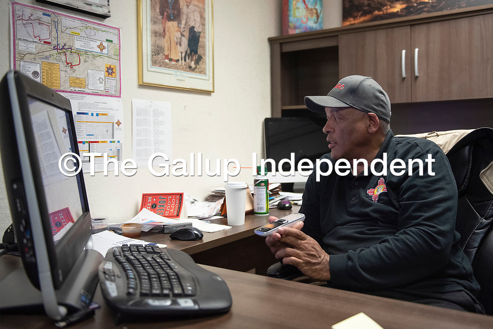 Tommy Mims, director of the Gallup Express looks at a bus schedule on his wall as he answers a call about bus routes Tuesday afternoon in Gallup. Gallup Express was awarded the New Mexico Rural Transit System of the Year for 2018.