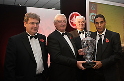 CARDIFF, WALES - Wednesday, November 11, 2009: Wales' Ashley Williams is presented with the Welsh Player of the Year trophy by SA Brains' Chairman John Rhys, President Phil Pritchard and General Secretary David Collins during the Football Association of Wales Player of the Year Awards hosted by Brains SA at the Cardiff City Stadium. (Pic by David Rawcliffe/Propaganda)