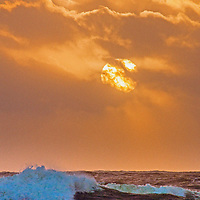 The sun sets over breaking waves in the Pacific Ocean near Moss Beach, California.