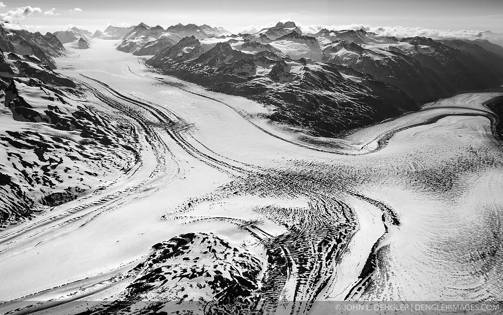 The uppermost portion of the Grand Pacific Glacier appears like a road intersection in Tatshenshini-Alsek Provincial Park. The Grand Pacific Glacier flows downward toward the Gulf of Alaska in the flow in the top left, and downward to to the upper reach of Glacier Bay National Park in the bottom left and right flows. The top right flow is the Melbern Glacier. Tatshenshini-Alsek Provincial Park is located in the very northwestern corner of British Columbia, Canada. The park sits between Kluane National Park and Reserve in the Yukon and Glacier Bay and Wrangell-St. Elias National Parks and Preserves in Alaska. All together, they form the largest protected area in thew world, approximately 21 million acres. The Tatshenshini and Alsek Rivers are protected in their entirety making them the only large watershed in North America that is totally protected.<br /> <br /> The remote park is known for its spectacular glacier and icefields, rafting and kayaking, hiking and mountaineering. Tatshenshini-Alsek Provincial Park is home to grizzly bears, Dall's sheep, wolves, mountain goats, moose, eagles, falcons, and trumpeter swans.<br /> <br /> The park was designated a UNESCO World Heritage site in 1994.