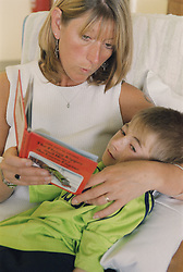 Young boy who is waiting for a Baclofen Implant pump operation; lying on mother's lap while she reads to him; on Children's ward in hospital,