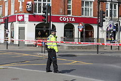 © Licensed to London News Pictures. 28/05/2021. London, UK. A police officer guards a crime scene outside Costa Coffee on High Road, Wood Green, north London, following a death of a man. Police were called at just after 1am on Friday, 28 May to reports of a firearm discharge in the vicinity of Turnpike Lane. Police officers, the London Ambulance Service and London's Air Ambulance attended the scene. A man, believed to be aged in his 20s, was found suffering a gunshot injury. Despite the efforts of the emergency services he was pronounced dead at the scene at just before 2am. Photo credit: Dinendra Haria/LNP