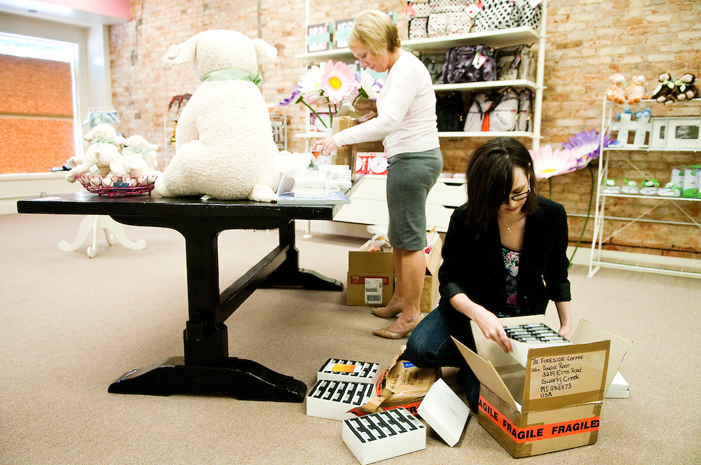 Matt Dixon | The Flint Journal..Angie Root (right), 28, of Swartz Creek unpacks boxes with her mother, Carol, Davis, 55, at Root's store The Baby Love Shoppe on E. Main Street in Flushing Monday afternoon. The store which opens May 7th will sell a variety of baby accessories and items.