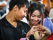 "14 FEBRUARY 2017 - BANGKOK, THAILAND:  A couple waits to get married in the Bang Rak district in Bangkok. Bang Rak is a popular neighborhood for weddings in Bangkok because it translates as ""Village of Love."" (Bang translates as village, Rak translates as love.) Hundreds of couples get married in the district on Valentine's Day, which, despite its Catholic origins, is widely celebrated in Thailand.     PHOTO BY JACK KURTZ"