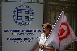 June 17, 2017 - Athens, Attiki, Greece - An avtivist with a feminist flag in front of the Asylum Service..Activists demonstrate in the Asykum Service of the Helenic .Republic with the main slogan been '' How many more lives' asking for support towards refugees and a stopage in the drownings of refugees that try to cross the Greek borders by sea. (Credit Image: © George Panagakis/Pacific Press via ZUMA Wire)