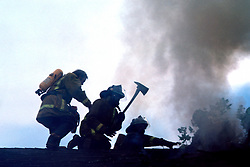 Stock photo of Houston fire fighters hacking through a roof for access to a burning house
