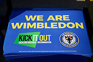 AFC Wimbledon Kick it out poster on seats during the EFL Sky Bet League 1 match between AFC Wimbledon and Peterborough United at the Cherry Red Records Stadium, Kingston, England on 18 January 2020.