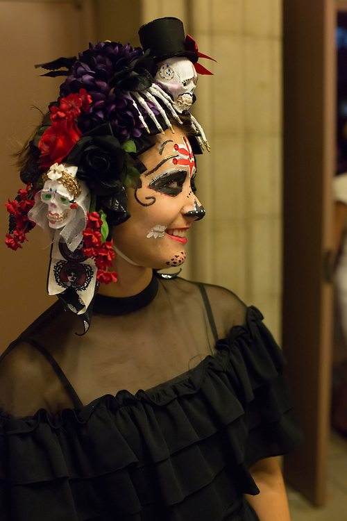 A woman with an elaborate hat which includes dia de los muertos skulls and face painting outside the ball.