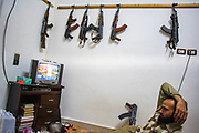 Kalashnikov assault rifles hang on the wall as Free Syrian Army (FSA) member Abu Fida (29), married from Kafr Bissin a township near Anadan, which is a suburb of Aleppo, northern Syria, watches the TV news at the FSA facilities in Marea on Monday, May 28, 2012. Abu Fida is a former Syrian state police officer who defected from his government's authorities because he was asked, as he claims, to kill innocent civilians in Syria. (Photo by Vudi Xhymshiti)