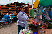 A woman sells sausage and meat during a party in the main square of Boca Colorado, Peru. Boca Colorado is a town formed entirely by mining activity in the Peruvian Amazon.