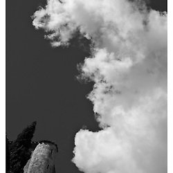 A black and white print of a large white cloud over the corner of a small castle.