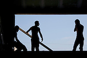 silhouette of 3 construction workers while working on a house