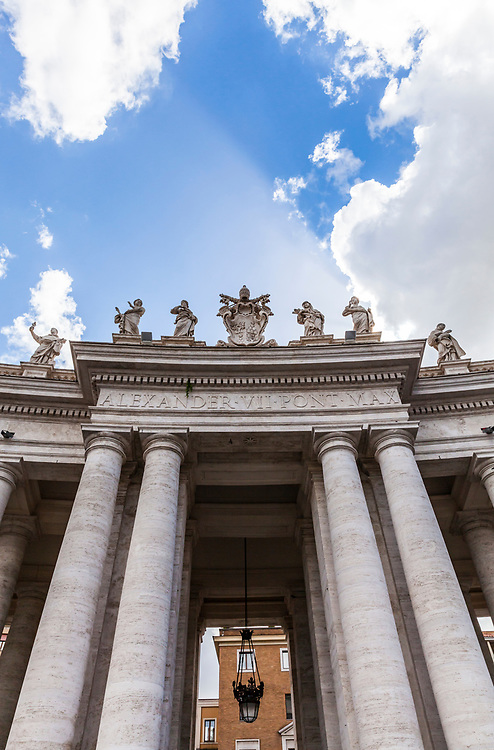 The southern entrance to St. Peter's Square through the colonnade, marked by a coat of arms of Alexander VII, Vatican City, Rome, Italy.