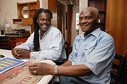 Carer sharing a drink with elderly man,