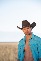 hot cowboy with green eyes in an open Western shirt outdoors